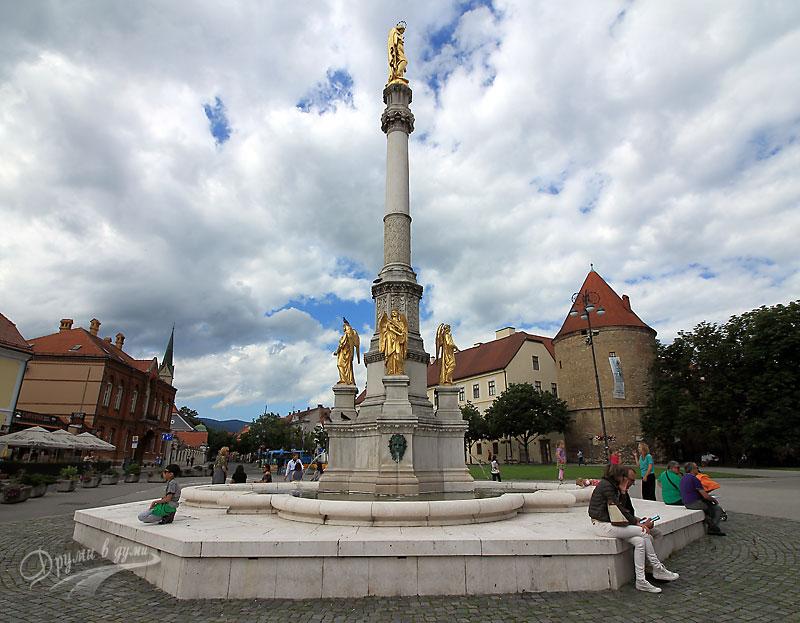 Загреб: статуята на Дева Мария с четири ангела, в далечината - Епископския дворец