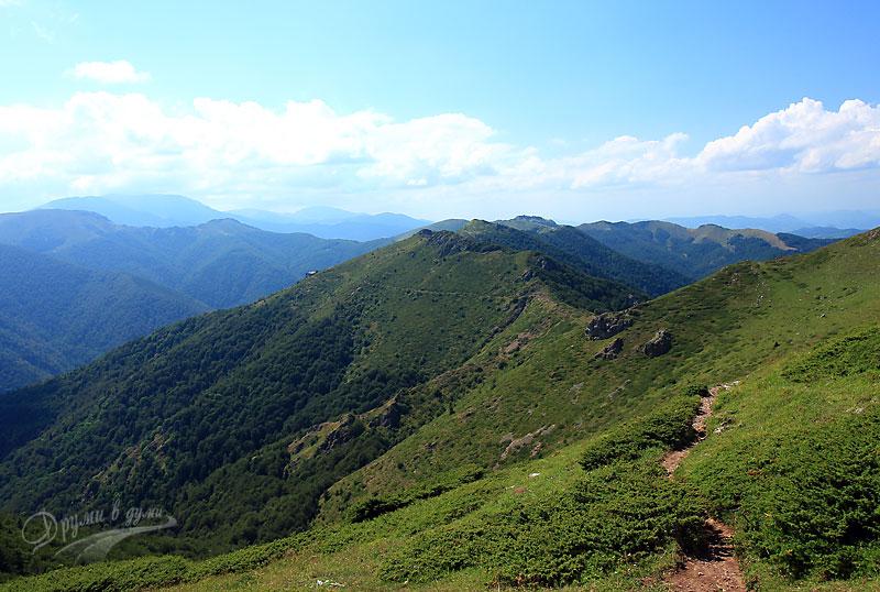 В далечината: хижя Козя стена, гледка от седловината под връх Боба