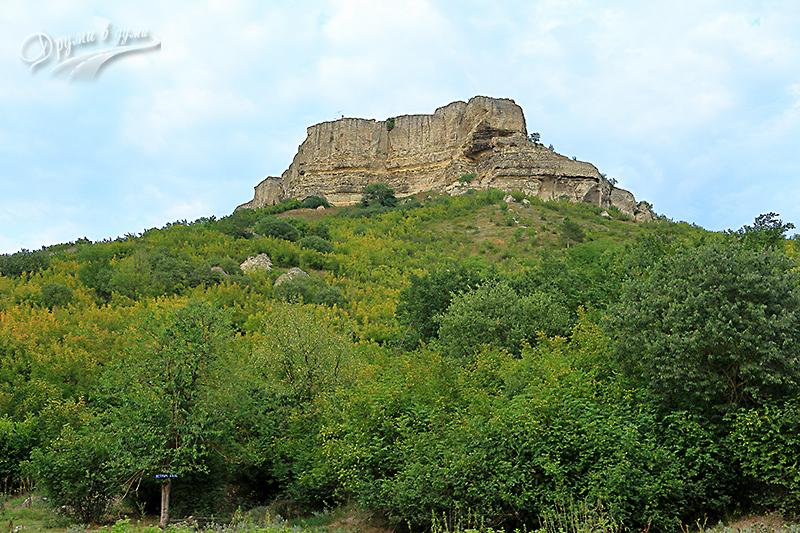 Ориентир от чешмата - крепост Петрич кале горе на платото и табелката долу в ляво