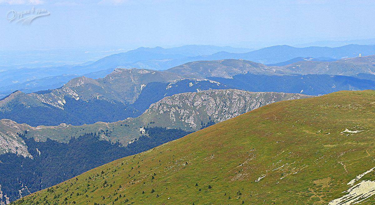 Гледка от връх Вежен: в центъра е връх Юмрука, по средата най-вляво е хижа Ехо,  над нея леко вдясно е хижа Козя стена, горе вдясно се белее арката на Беклемето