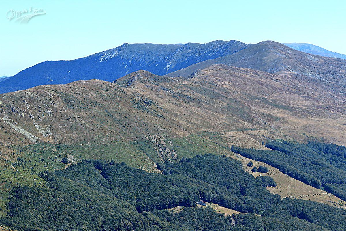 Гледка напред: вторият връх от ляво надясно в далечината е Вежен и неговият северен ръб, най-долу се вижда хижа Свищи плаз.